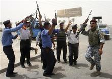 <p>Le forze di sicurezza irachene festeggiano il ritiro degli Stati Uniti a Baghdad oggi. REUTERS/Ahmed Malik</p>