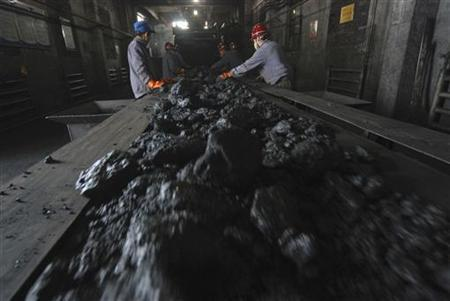 Employees work beside a conveyor belt at a coal mine workshop in this April 15, 2008 file image. REUTERS/Stringer