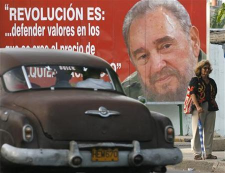 A vintage car moves past a portrait of Cuba's former leader Fidel Castro in Havana July 1, 2009. REUTERS/Enrique De La Osa
