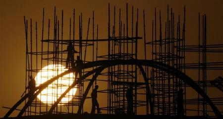 Labourers work at a construction site as sun sets in New Delhi in this February 16, 2008 file photo. REUTERS/Adnan Abidi/Files