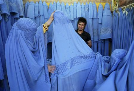 An Afghan woman looks at merchandise at a burqa shop in Herat in western Afghanistan July 2, 2009. REUTERS/ Mohammad Shoiab