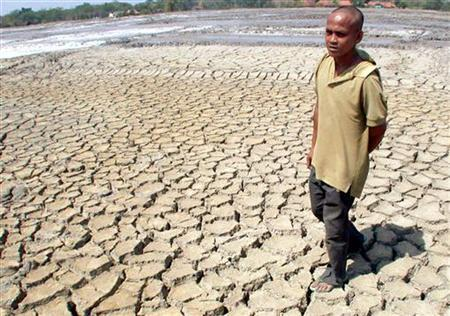 An Indonesian villager walks over dry land in Purwodadi in central Java August 28, 2002. REUTERS/Stringer