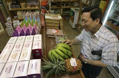 <p>A man inspects organic bananas from central Taiwan which are five times more expensive than regular bananas at an organic food chain store in Taipei June 30, 2009. Affluence and sedentary lifestyles have brought health problems such as obesity and diabetes to Asia, prompting locals to fill up their shopping carts with products such as oats, yoghurt and vitamins. REUTERS/Pichi Chuang</p>