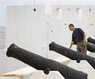 <p>U.S. President Barack Obama looks over the wall alongside cannons during his tour of the Cape Coast Castle, a former slave holding facility, in the town of Cape Coast, Ghana, July 11, 2009. REUTERS/Jason Reed</p>
