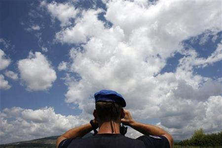 An observer from the European Union Monitoring Mission inspects an area near South Ossetia's de-facto border some 80 km (50 miles) north-west of Tbilisi July 10, 2009. REUTERS/David Mdzinarishvili