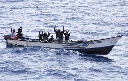 Suspected Somali pirates raise their hands in their skiff during their arrest by Marines from NATO's Portuguese frigate Corte-Real in the Gulf of Aden June 22, 2009. REUTERS/NATO/Carlos Dias/Handout/Files