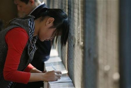 A job seeker fills in an application form at a 'talent market' in China's southern city of Shenzhen February 3, 2009. REUTERS/Bobby Yip