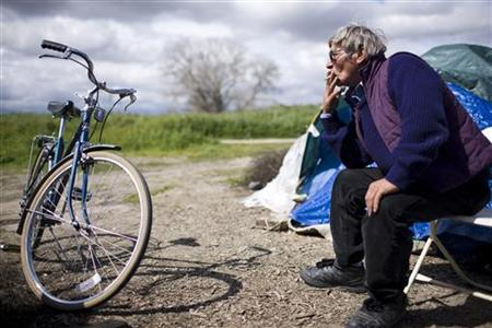 Gennadiy Tomashov smokes outside his tent at a homeless tent city in Sacramento, March 15, 2009. REUTERS/Max Whittaker