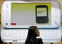 <p>Una mujer camina cerca de una imagen del modelo N97 de Nokia en Singapur, 15 jun 2009. El mayor fabricante de teléfonos móviles del mundo, el grupo finlandés Nokia, rebajó el jueves sus previsiones de rentabilidad para el segundo semestre y de participación de mercado en el 2009 para su filial de celulares, lo que provocó que sus acciones sufrieran una fuerte caída. REUTERS/Vivek Prakash/Archivo</p>