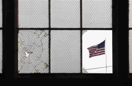 In this photo, reviewed by the U.S. military, an American flag flutters in the wind, pictured through a broken window from inside an unused airplane hangar used for media activities at Camp Justice, the site of the U.S. war crimes tribunal compound, at Guantanamo Bay U.S. Naval Base, Cuba, July 16, 2009. REUTERS/Brennan Linsley/Pool