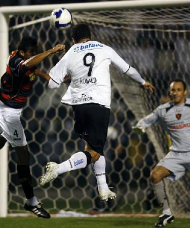 Corinthians' Ronaldo (9) heads the ball to score against Sport's goalkeeper Magrao (R) during their Brazilian championship soccer match in Sao Paulo July 16, 2009. REUTERS/Paulo Whitaker