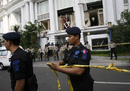 Policemen set up a cordon in front of the damaged Ritz-Carlton hotel after an explosion in Jakarta July 17, 2009. REUTERS/Supri