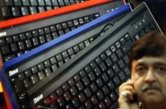 <p>Homem fala em celular diante de anúncio de abertura de feira de tecnologia Mumbai.</p>