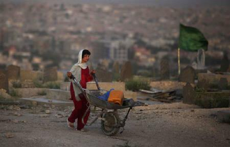 A girl pushes a wheelbarrow in Kabul July 19, 2009. Almost 30 years of conflict have forced millions of Afghan children to go without education and work to help feed their families, U.N. and Afghan government figures released on Wednesday showed. REUTERS/Ahmad Masood/Files