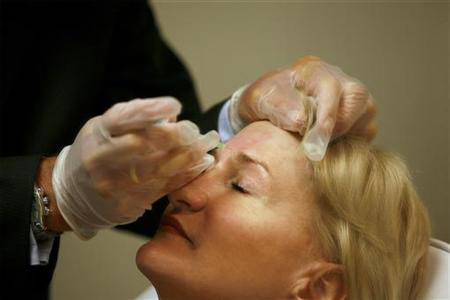 A doctor (L) shows the location of a Botox injection on the forehead of a patient after administering the injection at a walk-in Botox salon in New York July 17, 2007. REUTERS/Lucas Jackson