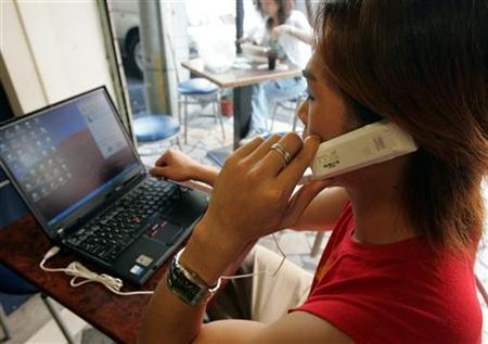 A man uses a Skype internet phone next to a laptop in Taipei November 11, 2005. REUTERS/Richard Chung