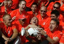 <p>Lewis Hamilton festeggia la vittoria insieme al team McLaren. REUTERS/Karoly Arvai (HUNGARY SPORT MOTOR RACING)</p>