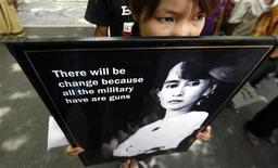 <p>Un'attivista protesta a Nuova Delhi con la fotografia della leader dell'opposizione Aung San Suu Kyi. REUTERS/Adnan Abidi</p>