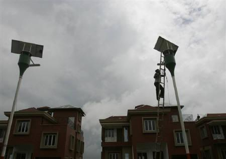A labourer checks the solar panel of a street light at a solar housing complex in Kolkata in this July 8, 2008 file photo. REUTERS/Parth Sanyal