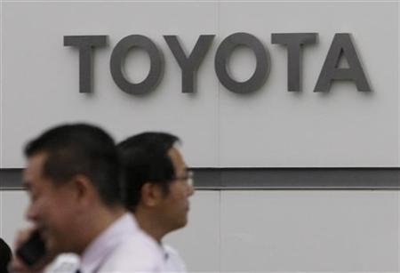 Men walk past a logo of Toyota Motor Corp at its Tokyo branch June 23, 2009. REUTERS/Kim Kyung-Hoon
