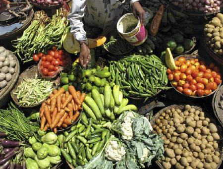 A vendor sprays water on vegetables to keep them fresh at a market in Siliguri July 6, 2009. India's wholesale price index (WPI) is forecast to have fallen 1.46 percent in the 12 months to July 18, steeper than the previous week's decline of 1.17 percent, a Reuters poll of 11 analysts showed on Wednesday. REUTERS/Rupak De Chowdhuri