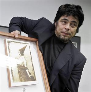Puerto Rican actor Benicio del Toro holds his Tomas Gutierrez Alea prize at Cuban Union of writers and actors in Havana, July 30, 2009. REUTERS/Enrique De La Osa