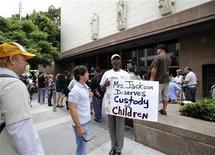<p>Homem segura cartaz em apoio à mãe de Jackson, em frente ao tribunal onde se realizou a audiência, em Los Angeles. REUTERS/Phil McCarten</p>