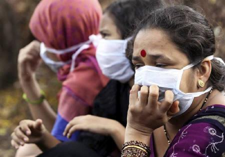 Women wearing masks wait to receive medical attention for suspected H1N1 influenza at a hospital in Pune August 4, 2009. The World Health Organisation stuck on Tuesday to its statement that about two billion people could catch H1N1 influenza by the time the flu pandemic ends. REUTERS/Stringer
