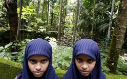 <p>Eleven-year-old twin sisters Rasheena M. (L) and Sameena M. pose for a photograph in Kodinji village in the southern Indian city of Kerala July 28, 2009. REUTERS/Arko Datta</p>