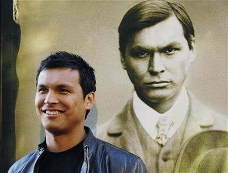 Adam Beach, a cast member in the HBO film ''Bury My Heart at Wounded Knee,'' poses alongside a portrait of his character Charles Eastman on a poster at the premiere of the film in Los Angeles, May 10, 2007. REUTERS/Chris Pizzello
