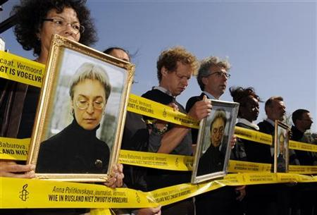 Protesters hold pictures of murdered Russian journalist Anna Politkovskaya during a demonstration against the visit of Russia's President Dmitry Medvedev in Amsterdam June 19, 2009. . REUTERS/Toussaint Kluiters/United Photos (NE RLANDS