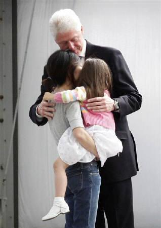 Freed U.S. journalist Euna Lee (L) is embraced by her daughter Hana Saldate and former U.S. President Bill Clinton after arriving with fellow freed U.S. journalist Laura Ling from North Korea in Burbank, California August 5, 2009. REUTERS/Danny Moloshok