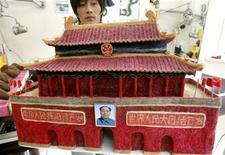 <p>Cabeleireiro chinês Huang Xin com a réplica do Portão da Paz Celestial em Pequim. 03/08/2009. REUTERS/David Gray</p>