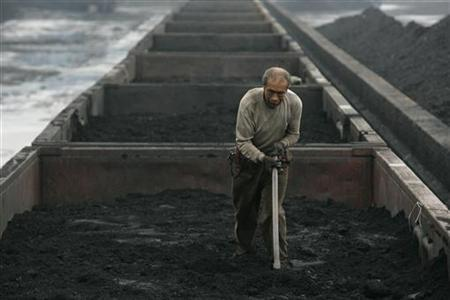 A worker levels out a load of coal inside a railroad truck at a coal dump site in Taiyuan, Shanxi province July 27, 2009. REUTERS/Stringer