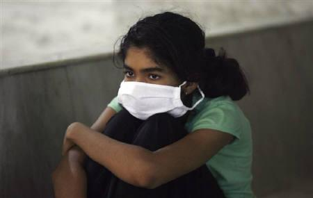 A girl wears a mask prior to being tested H1N1 influenza at a special ward in Kasturba Hospital, in Mumbai August 5, 2009. REUTERS/Punit Paranjpe