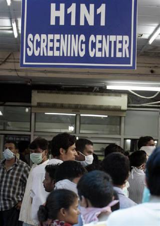 People wearing masks wait in a queue for a H1N1 flu screening at a hospital in New Delhi August 11, 2009. REUTERS/Fayaz Kabli