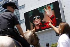 <p>A fan points at a monitor revealing a picture of Michael Jackson as a mounted police officer looks on outside the Staples Center following a memorial service for Jackson in Los Angeles July 7, 2009.REUTERS/Joshua Lott</p>
