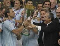 <p>Sebastiano Siviglia (a sinistra) e il presidente della Lazio Claudio Lotito (a destra) alzano il trofeo della Supercoppa, vinta contro l'Inter a Pechino, 8 agosto 2009. REUTERS/Jason Lee</p>