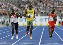 <p>O jamaicano Usain Bolt (c) sorrindo ao chegar ao final da prova nos 100 metros rasos durante do Mundial de Atletismo em Berlim. REUTERS/Michael Dalder</p>