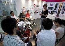 <p>Chen Xiangru, the founder of sex toy company 'Sweet Secrets', speaks to her sales staff about the uses of dildos at her shop located in a building dedicated entirely to sex products in Beijing August 18, 2009. REUTERS/David Gray</p>