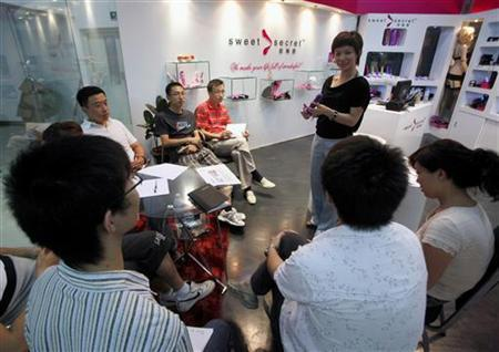 Chen Xiangru, the founder of sex toy company 'Sweet Secrets', speaks to her sales staff about the uses of dildos at her shop located in a building dedicated entirely to sex products in Beijing August 18, 2009. REUTERS/David Gray