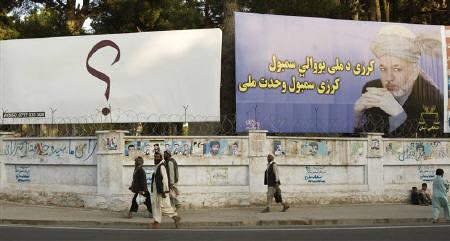 Afghans walk past election billboard of Afghanistan's President Hamid Karzai in Herat, western Afghanistan August 18, 2009, file photo. REUTERS/Raheb Homavandi