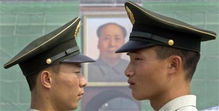 Military policemen stand guard in front of a portrait of China's late Chairman Mao Zedong at Tiananmen Gate, which is under renovation, in Beijing August 14, 2009. China's normally secretive Defense Ministry on Thursday launched a website (www.mod.gov.cn), in a new bid to allay overseas criticism over its military transparency and the build-up of its armed forces. REUTERS/Jason Lee