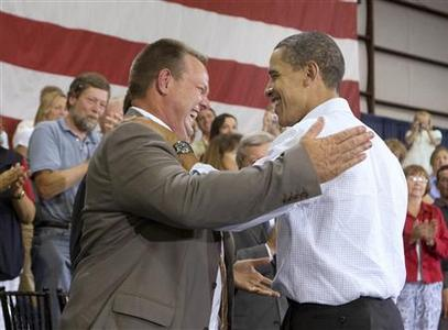 U.S. President Barack Obama (R) shakes hands with U.S. Sen. Jon Tester after a town hall meeting on healthcare inside a hangar at Gallatin Field in Belgrade, Montana, August 14, 2009. REUTERS/Larry Downing