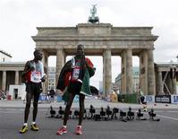 <p>Os quenianos Abel Kirui (à direita) e Emmanuel Kipchirchir posam em frente ao Portão de Brandenburgo em Berlim após ganhar primeiro e segundo lugares na maratona masculina do Mundial de Atletismo. REUTERS/Wolfgang Rattay</p>