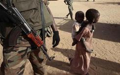 <p>Piccole profughe sudanesi accanto a un soldato della missione di peacekeeping Unamid per il Darfur. REUTERS/Zohra Bensemra</p>