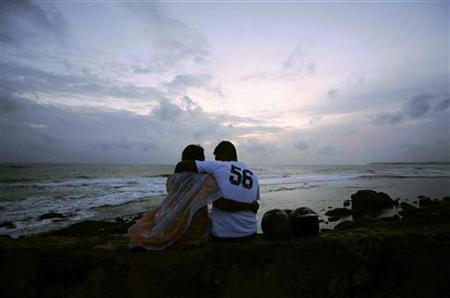 A couple sits on the ramparts of the 16th century Dutch fort that encloses part of Galle, August 17, 2009. REUTERS/Vivek Prakash