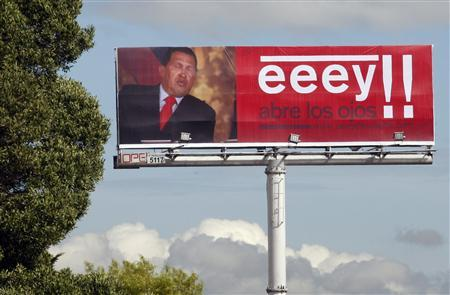 A billboard is seen with a photo of Venezuela's President Hugo Chavez and a sentence that reads: ''Hey!! Open Your Eyes'' in Bogota, August 27, 2009. REUTERS/Jose Miguel Gomez