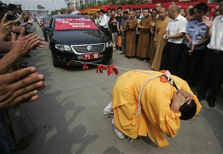 Zhang Tingting, 52, pulls cars with her hair during a performance in Kaifeng, Henan province August 25, 2009. Zhang succeeded in pulling eight cars over 20 metres with her one-metre-long braid, local media reported. REUTERS/Stringer