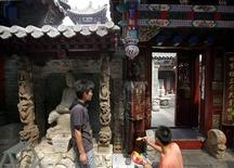 <p>Artist Liu Bolin (C), also known as the 'Vanishing Artist', is painted by assistants as he makes himself look exactly the same as the wall of an old temple in a Hutong in central Beijing August 26, 2009. REUTERS/David Gray</p>